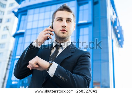 Businessman talking on a cell phone looking at the time on the background of office building