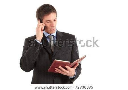 Businessman talking on a mobile phone while reading his agenda - stock photo
