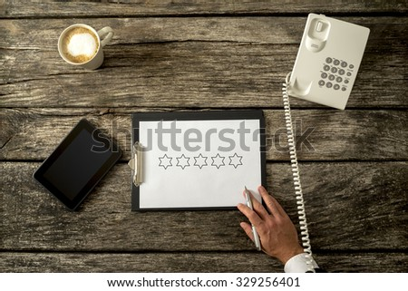 Businessman talking on a phone with five stars for quality visible on a notepad on a clipboard on a rustic wooden desk or table with a tablet alongside in a conceptual image, overhead view. - stock photo