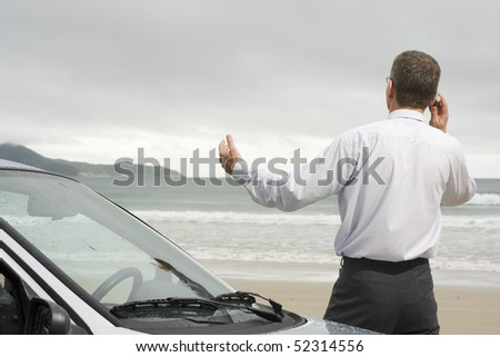 Businessman talking on cell phone beside his car on a beach - stock photo