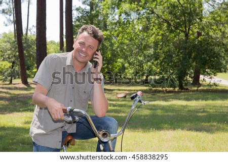 Businessman talking on cell phone holding his cycle. Joyful man holding bicycle and talking on mobile phone.