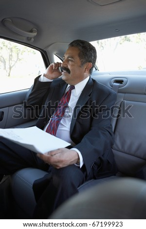 Businessman talking on cell phone in car