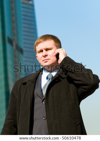 Businessman talking on cell phone on skyscrapers background - stock photo