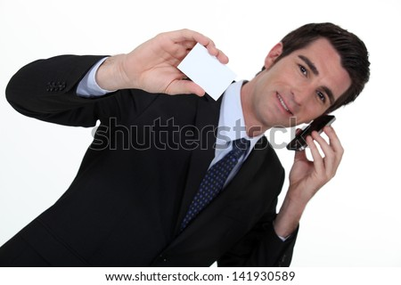 Businessman talking on his mobile phone and holding a card - stock photo