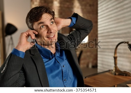Businessman talking on mobile, hand behind ears, looking up. - stock photo
