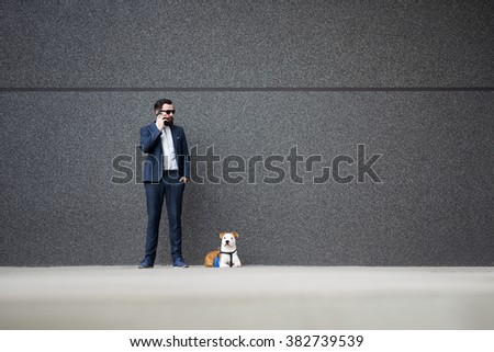 Businessman talking on mobile phone and holding his dog on leash.