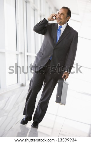 Businessman talking on mobile phone in office lobby - stock photo