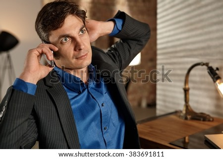 Businessman talking on mobilephone, looking away. - stock photo