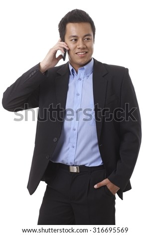 Businessman talking on mobilephone, looking away, standing with hand in pocket. - stock photo