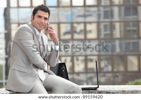 Businessman talking on phone in front of a laptop computer - stock photo