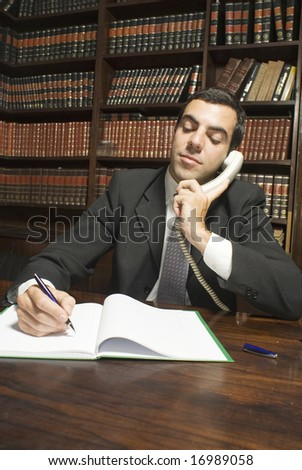 Businessman talking on phone writing in a notebook. Vertically framed photo.