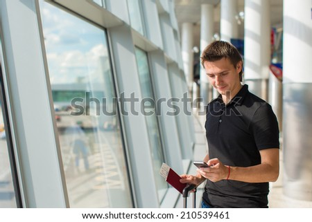 Businessman talking on smartphone walking inside in airport - stock photo