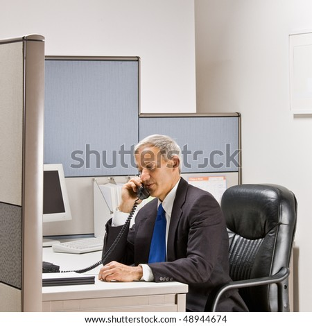 Businessman talking on telephone at desk
