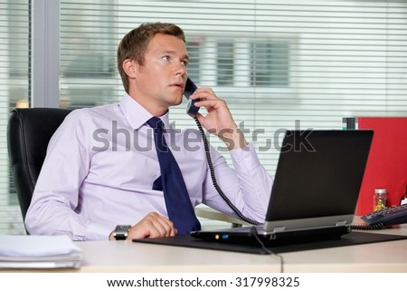 Businessman talking on telephone at office with laptop on table