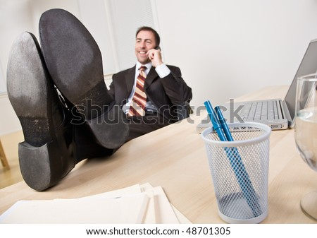 Businessman talking on telephone with feet up - stock photo