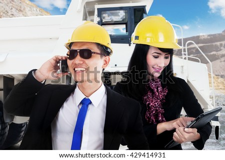 Businessman talking on the cellphone while his partner using a digital tablet with mining truck on the background - stock photo