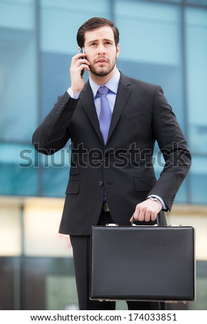 businessman talking on the phone in front of an office building with a briefcase in hand