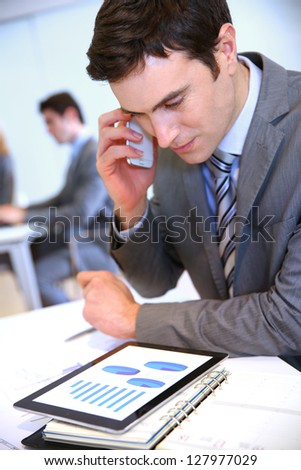 Businessman talking on the phone in office - stock photo