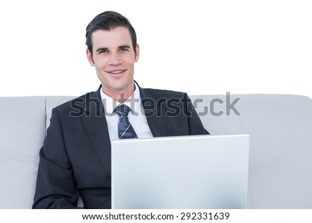businessman talking on the phone on the sofa with his laptop against a white wall