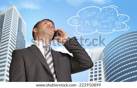 Businessman talking on the phone. Skyscrapers and cloud with business sketches in background - stock photo