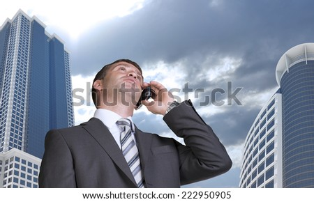 Businessman talking on the phone. Skyscrapers and clouds in background