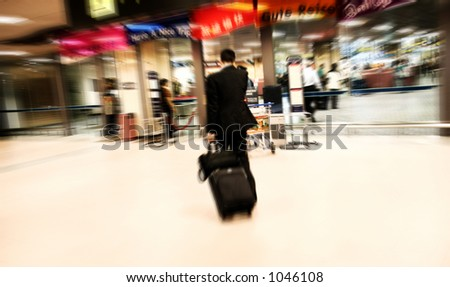 Businessman talking on the phone while rushing to immigration at the airport. Intentional Zoom-effect motion blur. - stock photo