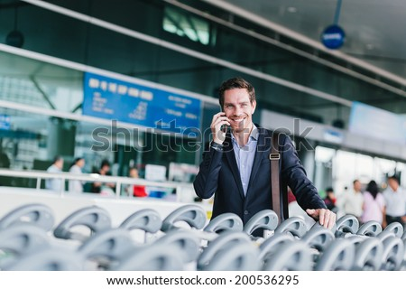 Businessman talking on the phone while standing near rows of luggage trolleys in the airport - stock photo