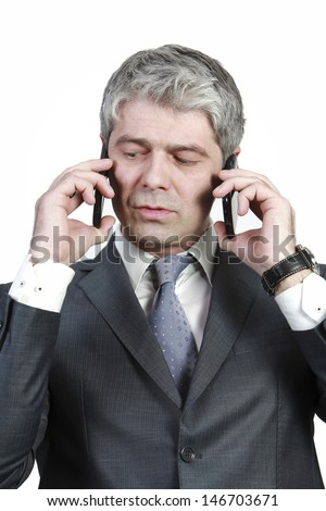 Businessman talking simultaneously on two cell phones... under pressure.../Hold on I have a second line - stock photo
