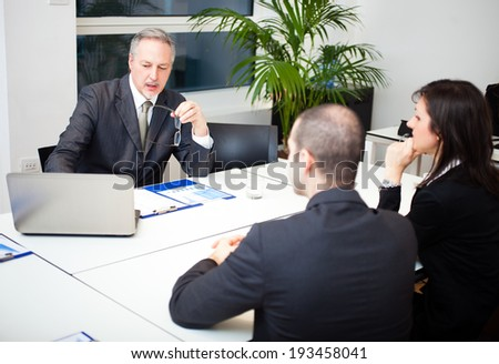 Businessman talking to a couple - stock photo