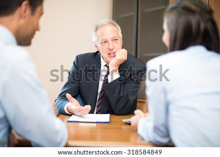 Businessman talking to a young couple - stock photo