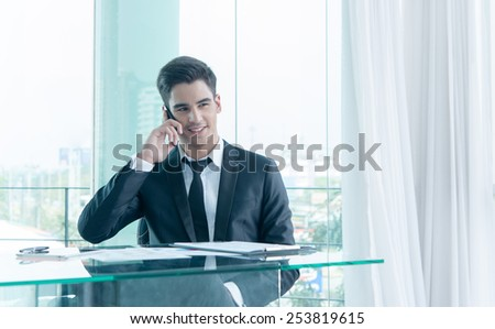 businessman talking via cell phone in office - stock photo