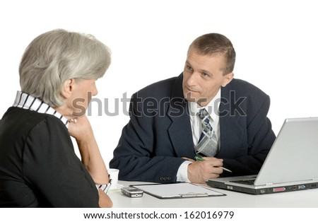 businessman talking with elderly woman at the table in office