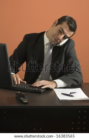 Businessman talks on the phone as he sits at his computer. Vertically framed photo. - stock photo