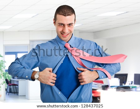 Businessman tearing his shirt like a superhero - stock photo