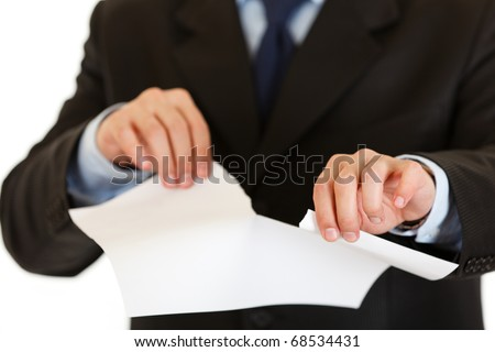 Businessman tearing sheet of white paper isolated on white. Close-up. - stock photo