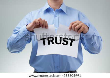 Businessman tearing up sign saying trust concept for infidelity, dishonesty and cheating - stock photo