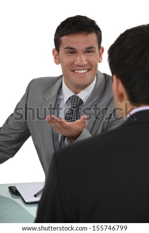 Businessman telling a joke to colleague - stock photo