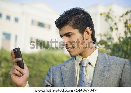 Businessman text messaging on a mobile phone - stock photo