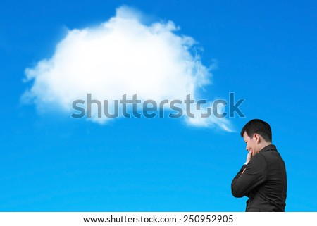 Businessman thinking about white cloud thought bubble above his head isolated on blue background - stock photo