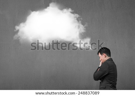 Businessman thinking about white cloud thought bubble above his head with concrete wall background - stock photo