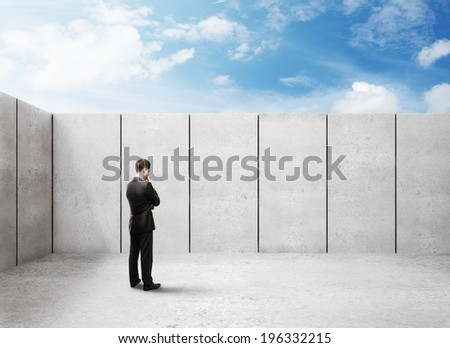 businessman thinking and looking at wall in office