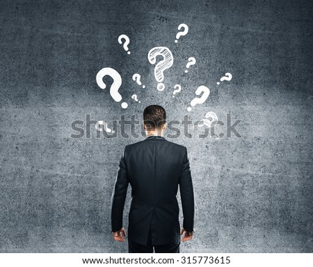 businessman thinking and looking on concrete wall - stock photo