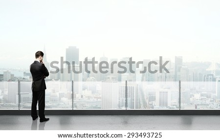 businessman thinking and standing on roof - stock photo
