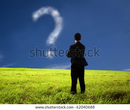 businessman thinking and watching the question mark.the  composition of the cloud - stock photo