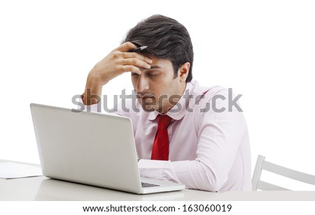 Businessman thinking in front of a laptop