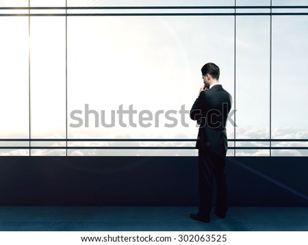 businessman thinking in office and looking to sky - stock photo