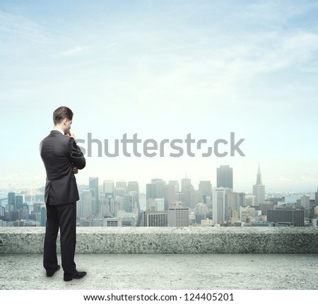 businessman thinking on roof and city background - stock photo