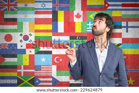 Businessman thinking over flags background - stock photo