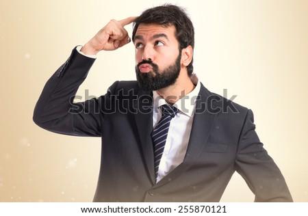 Businessman thinking over ocher background - stock photo