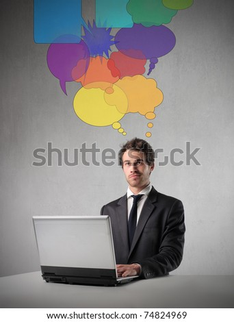 Businessman thinking while working on a laptop - stock photo
